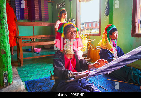 INLE LAKE, MYANMAR - FEBRUARY 18, 2018:  The long neck women of Padaung Kayan tribe attract the tourists to visit their traditional textile workshop a - Stock Photo