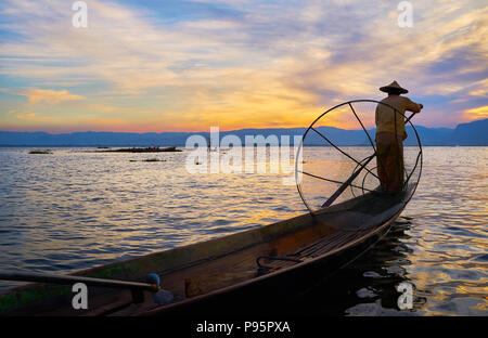 So-called 'one-legged fisherman' floats in his kayak with a paddle and conical net on sunset, Inle Lake, Intha, Myanmar. - Stock Photo