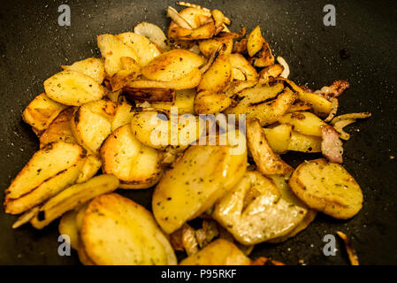 potatoes fried in oil in a frying pan, with herbs for autrian food - Stock Photo