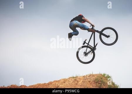mtb dirt rider doing trick on a jump - Stock Photo