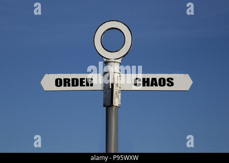 Old road sign with order and chaos pointing in opposite directions against a blue sky - Stock Photo