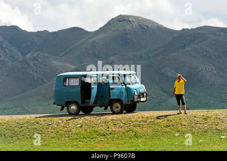 Local guide standing next to a UAZ off-road van in the Khögnö Khan Uul Nature Reserve, Bulgan province, Mongolia - Stock Photo