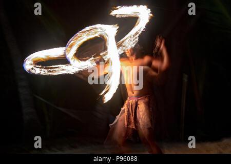 polynesian dancer using flame pole on black background - Stock Photo