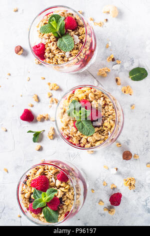 Yogurt parfafait with granola, jam and raspberries on stone table. Healthy dessert top view. - Stock Photo