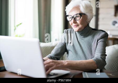 Senior woman typing on laptop - Stock Photo