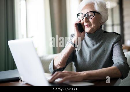 Senior woman having a conversation on the phone - Stock Photo