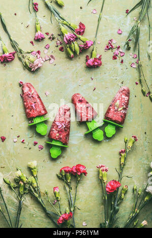 Red homemade fruits and berries ice cream or popsicles on teal rustic green table background, decorated with garden flowers, top view.  Country style  - Stock Photo