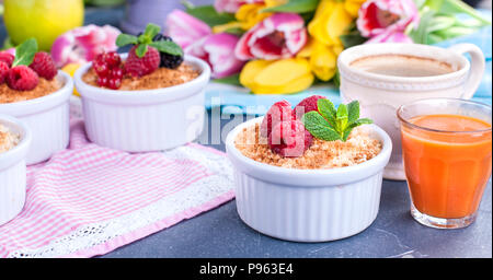 Sweet breakfast in portions with raspberries and mint. Homemade pastries and fragrant coffee, juice. A bouquet of spring flowers, yellow and pink tulips. Postcard or text - Stock Photo