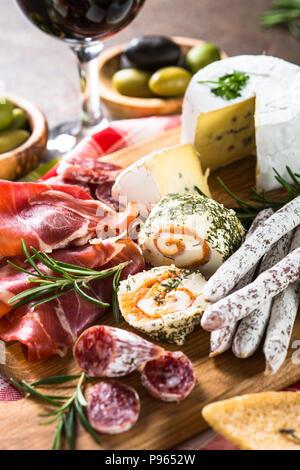Antipasto delicatessen - sliced meat, ham, salami, cheese, olives ciabatta on wooden board - Stock Photo