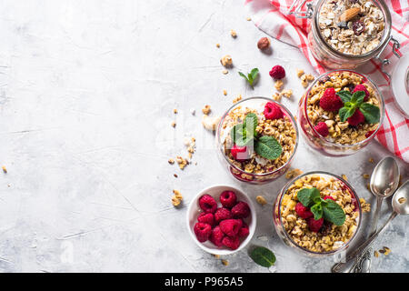 Yogurt parfafait with granola, jam and raspberries on stone table. Healthy dessert top view with copy space. - Stock Photo