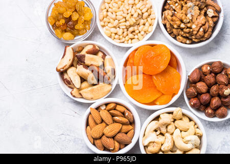 Assortment of nuts and dried fruits in bowls. Cashew, hazelnuts, walnuts, almonds, brazilian nuts, raisins, dried apricots and pine nuts. Top view wit - Stock Photo