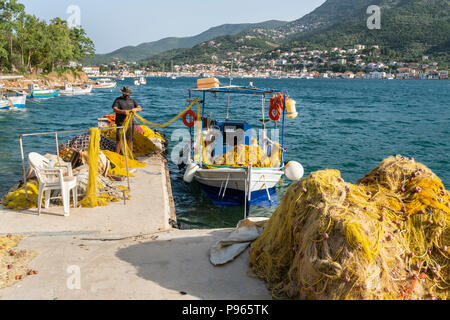 Fisherman and fishing nets on the North harbour quay in Vathy harbour with the town of Vathy in the background. On the island of Ithaca, Ionian Sea, G - Stock Photo