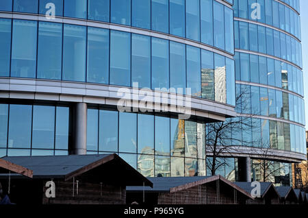 Glass modern office buildings at London Bridge City on the south bank of the River Thames in London, England. Tops of food stalls in foreground. - Stock Photo
