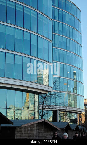Glass modern office buildings at London Bridge City on the south bank of the River Thames in London, England. Food stalls in foreground with people. - Stock Photo