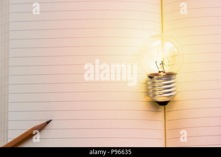 Concept idea. Growing light bulb on vintage book with pencil. Copy space for your text. conceptual great ideas are always available. Creative thinking - Stock Photo