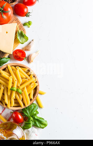 Italian food background. Pasta, tomatoes, herbs and vegetables on white table. Top view, Copy space. - Stock Photo