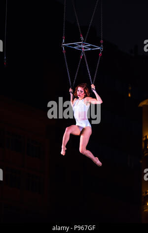 Bucharest, ROMANIA - July 14 2018: Sonics in Wish performance at Street Theater Festival. Graceful dancer performing aerial acrobatics on overturned s - Stock Photo