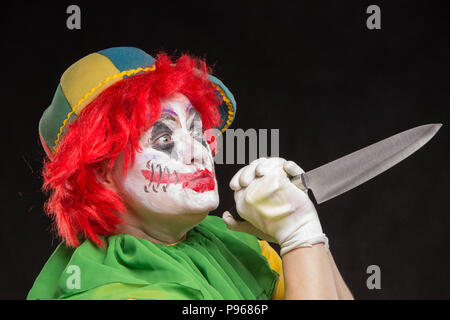Scary clown with a horrible make-up laughs and with big knives in hands on a black background - Stock Photo