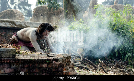 Sadhu preparing fire for ritual during the traditional Hindu festival Maha Shivaratri in the vicinity of Pashupatinath temple in Kathmandu, Nepal - Stock Photo