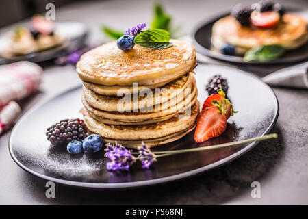 Pancakes with strawberries blackberries blueberries lavender and mint leaves. - Stock Photo