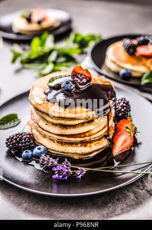 Pancakes with strawberries blackberries blueberries lavender mint leaves and hot chocolate. - Stock Photo