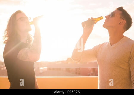 couple of young men drinking beer together under the sunset sunlight. bright image for beautiful males models in happiness and outdoor leisure activit - Stock Photo