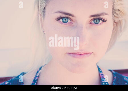 defocused portrait with focus on clear eye of a beautiful caucasian russina girl model young sit down and looking to you on camera. little smile relax Stock Photo