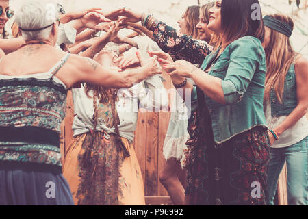 group of free and hippy rebel alternative style young women together dancing and celebrating with joy and happiness in a natural place indoor and outd - Stock Photo