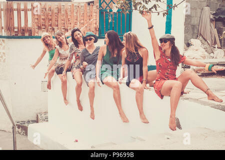 group of seven young smile beautiful woman crazy in vacation and friendship or relationship stay together sit down and go crazy with laugh. summer col - Stock Photo