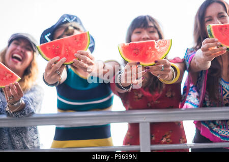 four nice happy young females caucasian eating watermelon to celebrate summer time and warm day with sun near the ocean. beautiful colors for group of - Stock Photo