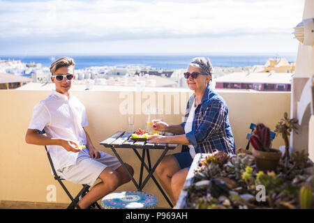 happy leisure activity on the terrace rooftop having breakfast with smiles and happiness for grandmother and teenager family caucasian people. ocean a - Stock Photo