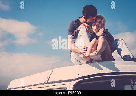 beautiful caucasian couple of natural model stay together in relationship on the roof of a vintage camper. friendship and love between girl and boy yo - Stock Photo