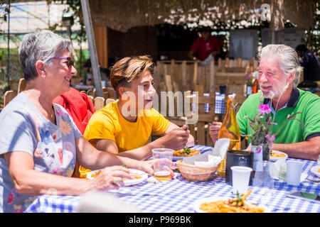 family caucasian people with grandmother grandfather grandson eating together in alternative natural place restaurant enjoying the meal and the vegeta - Stock Photo