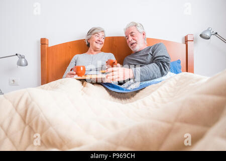 caucasian aged couple doing breakfast at home in the bed. nice natural scene at home for togheterness life concept. love and carefree people married.