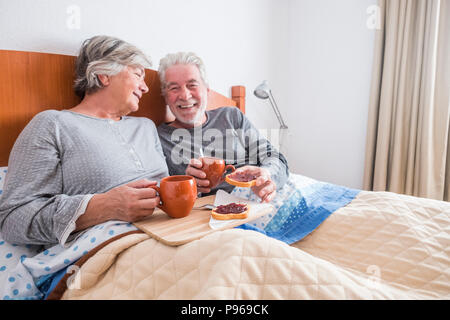 nice caucasian aged senior couple enjoying and laughing together waking up in the early morning. toasted and marmelade and coffee. togetherness and fo - Stock Photo