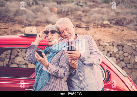 senior adult couple check and look mobile phones to connect with internet or take a photo selfie. vintage red car ready to travel and everywhere in th - Stock Photo
