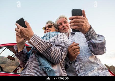 alternative point of view from the bottom for young senior couple caucasian people using smartphone to take pictures and connect to internet. travel a - Stock Photo