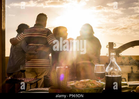people group of senior friends hug and celabrate together viewing the golde sunset from a rooftop terrace. living always in vacation and retired happi - Stock Photo