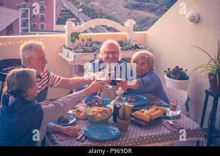 group of caucasian adult mature people eating and drinking together celebrating event by night on the rooftop with city and nature view. summer time a - Stock Photo