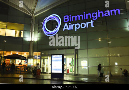 Exterior view of the terminal building at Birmingham International Airport at night with an illuminated sign of the airport's name - Stock Photo