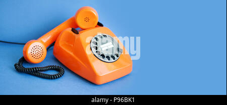 Busy retro phone orange color, handset receiver on blue background. copy space - Stock Photo
