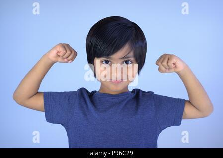 Portrait of young boy smiling looking at camera. Smart kid showing his arms muscles with fists - Stock Photo
