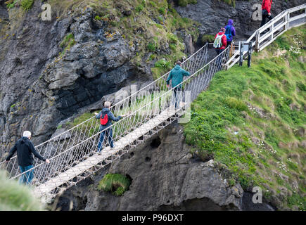 Tourists walking on the Carrick-a-Rede rope bridge on the Causeway Coast in County Antrim, Northern Ireland - Stock Photo