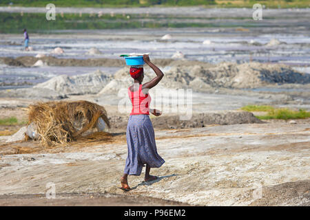 African Woman Walking Carrying Basin on Head, Africa Woman Carries Load on top of her Head, Uganda - Stock Photo