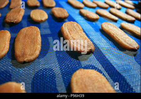 Dried banana on blue mesh, Dried fruit - Stock Photo