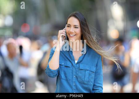 Happy woman in blue talks on phone walking on the street - Stock Photo