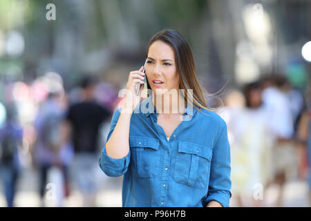 Serious woman in blue talks on phone walking on the street - Stock Photo