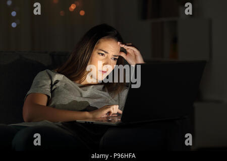 Portrait of a worried woman using a laptop in the night at home - Stock Photo