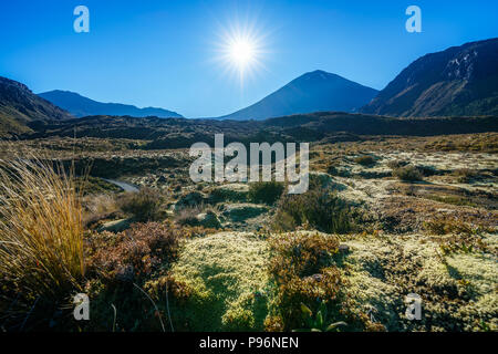 hiking the tongariro alpine crossing,sunstar over cone volcano mount ngauruhoe,new zealand - Stock Photo