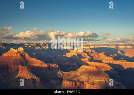 Sunlight at Grand Canyon seen from Mohave Point before sunset with some clouds in the sky - Stock Photo